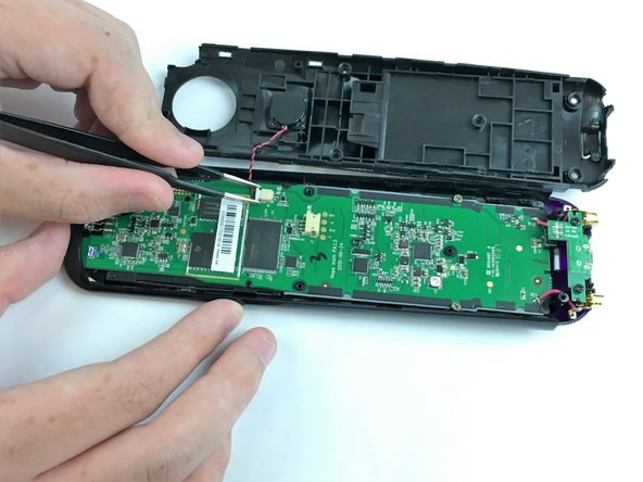 Use the Angled Tweezers to carefully pull the white cable end off of the remote and disconnect it.