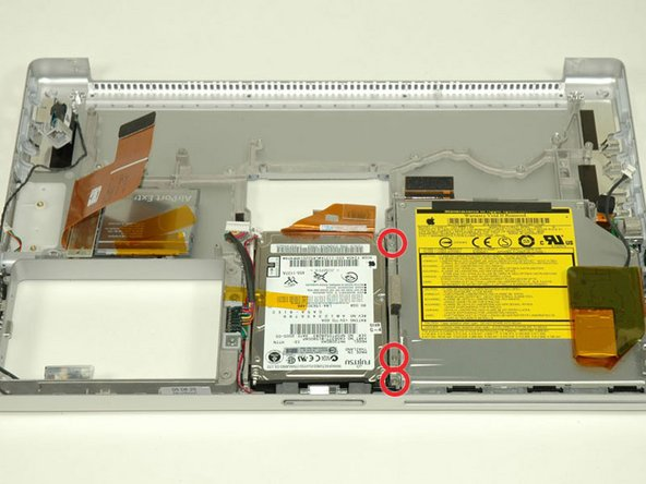 Remove the three long silver Phillips screws from the retaining bracket on the left side of the optical drive.