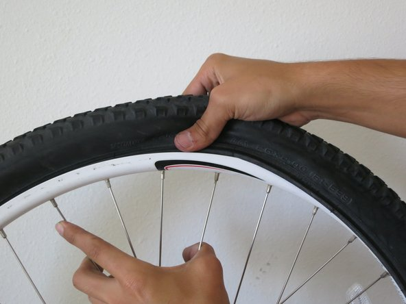 Once the tube is in, push the second side of the tire into the rim and continue all the way around the rim until the tire is inside the rim.