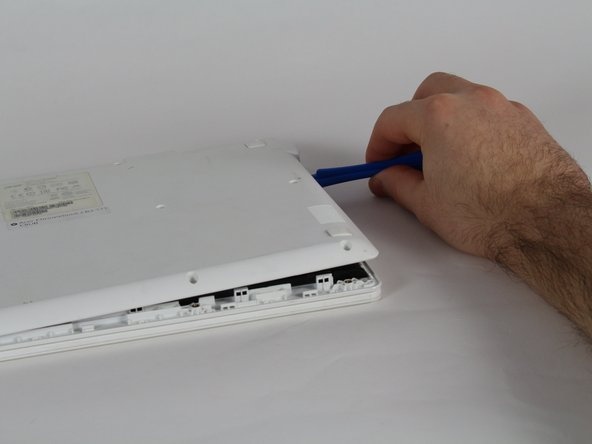 Image 1/3: Use the plastic opening tool to pry open then remove the plastic base from the rest of the laptop. Start from the right side and work towards the left.