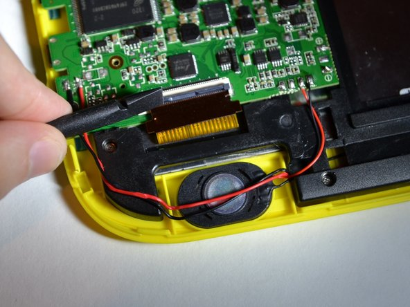 Use the flat end of the spudger to lift the black panel covering the ribbon cables.