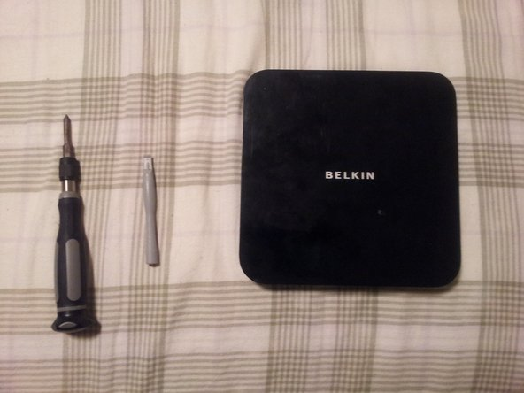 Image 1/1: Pictured here is the Belkin F5L009, along with a plastic opening tool and a #1 Philips (at least so the head says...), which were the only tools I needed to do this.  A guitar pick or other thin, flat, plastic object might work instead of an opening tool; I didn't test it.