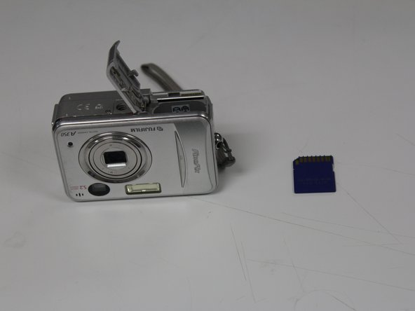 Image 3/3: The memory card is spring-loaded and will pop out of the camera far enough to be removed by hand.