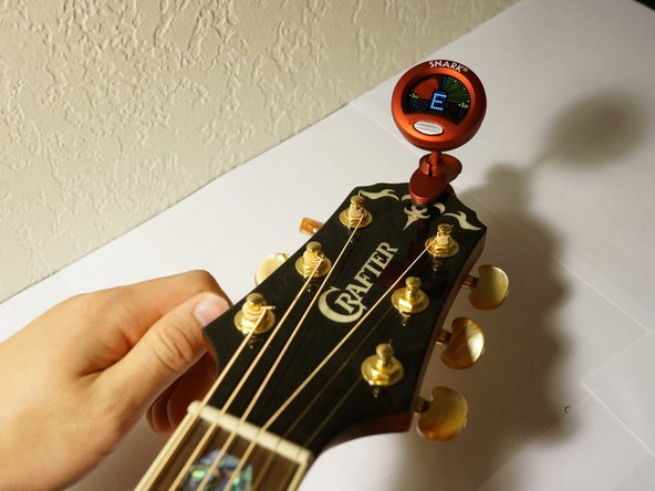 Clip the tuner on the head of the guitar and turn it on.