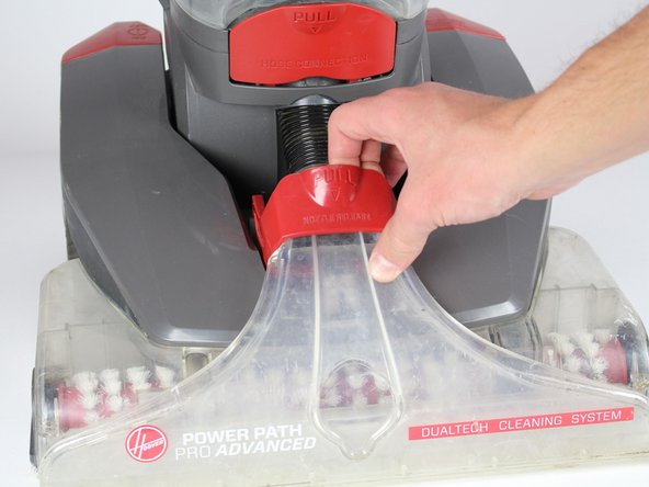 Pull the red handle to remove the front suction unit from the cleaner.