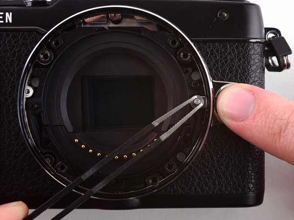Image 1/3: Use tweezers to remove the spring underneath the lens hook.