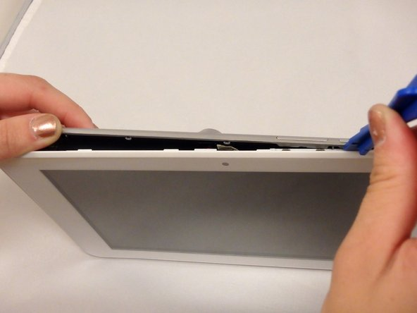 Slide the plastic opening tool along the sides and corners of the seam of the device while it separates from the screen.