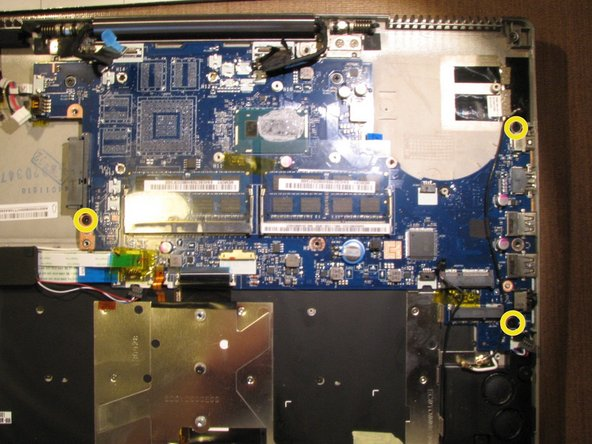 Image 1/2: Remove the motherboard by lifting it up very carefully as the power button ribbon cable is still connected to the left under side of the motherboard. See step 21.