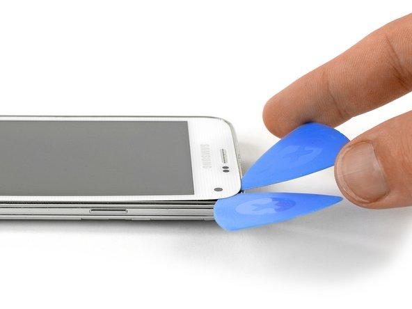 Setze ein drittes Plektrum ein und schiebe es bis zur oberen linken Ecke des Smartphones. Achte auf die Frontkamera und den Lautsprecher!