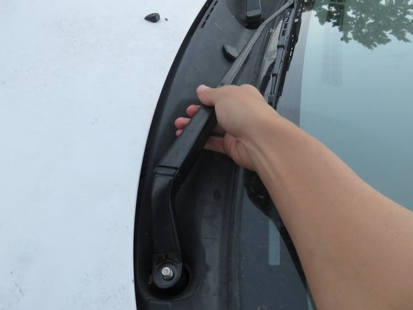 Firmly grip the lower end of the wiper arm.
