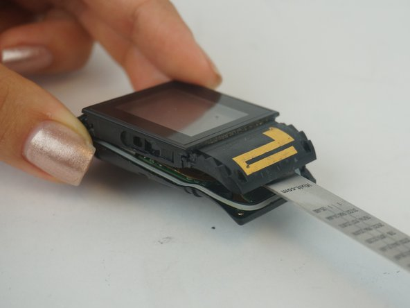 Use a thin tool to pry the the device apart by lodging it between the clock face and back side of the device.