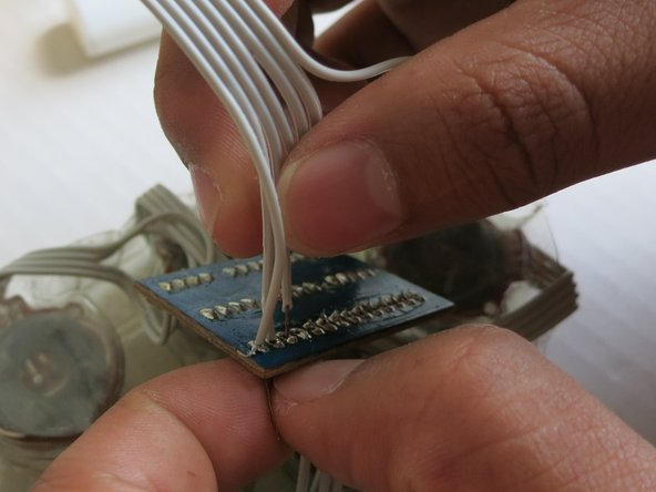 Image 1/3: Place each end of the loose wires through the holes you made in Step 7.