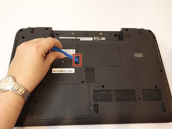 Use the plastic opening tool to pry open the RAM cover. Wedge the prying tool in, beginning at the indent in the cover.