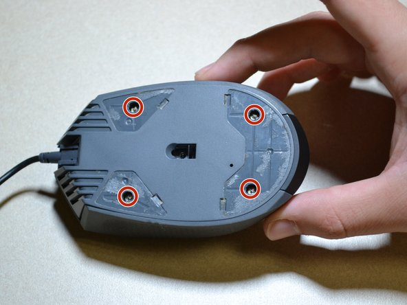 Use the JIS 0 screwdriver to remove the four 5 mm screws on the bottom of the mouse.