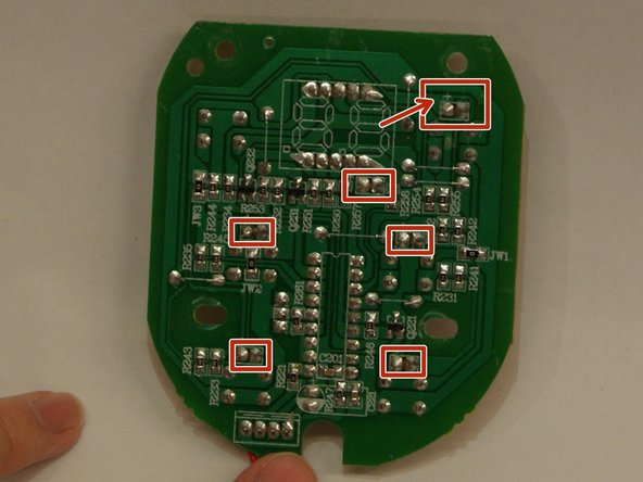 Heat each point with the soldering iron while pulling the LED out from the front in order to remove the lights. The arrow in the picture points to the + sign above the left solder point. Each of the LED solder points will have one. LED's are polarity sensitive; therefore, the positive pin on the new LED must match up to the positive solder point.