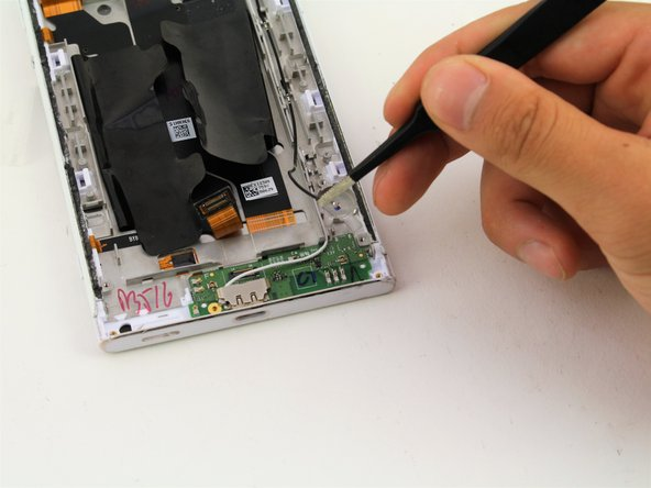 Grab the black wire connected to the charging port PCB board with your flathead tweezers.