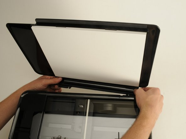 Remove the flap for the scanner. The flap is attached with two  clips that can be dislodged by pulling lightly away from the printer.