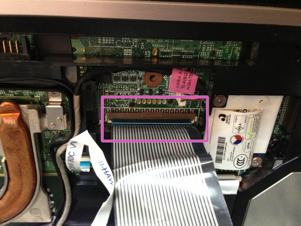 Image 1/3: Release the smaller ribbon cable by lifting up the white retainer