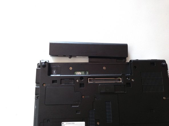 Image 3/3: Push release button to the left to release battery and gently pull battery from the laptop