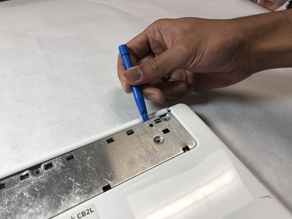 Starting at either the top left or right hand corner of the exposed metal piece, use the blue plastic opening tool to remove the back panel.