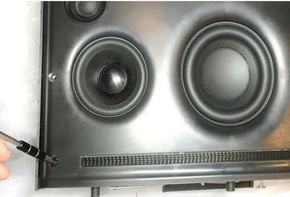 Use a pointed metal spudger to remove the rubber plugs covering  the screws in the bottom left and right corners of the speaker panel.