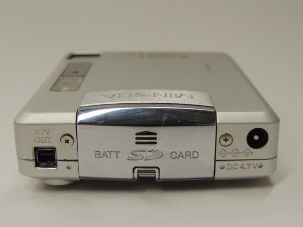 Locate the latch labeled BATT SD CARD on the right side of the camera.