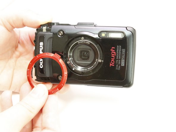 Remove the red ring surrounding the lens by twisting it counter-clockwise