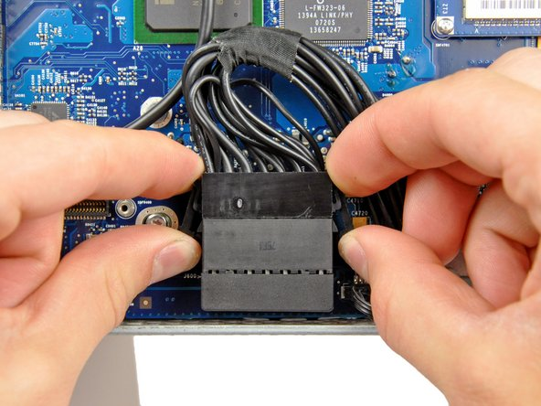 Disconnect the DC-In cable by simultaneously depressing both locking arms and pulling its connector away from the socket on the logic board toward the top of your iMac.