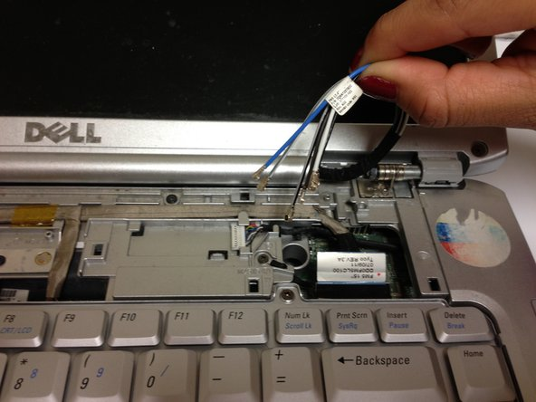 Pull the wires that you disconnected in the previous step through the hole in the top of the laptop.