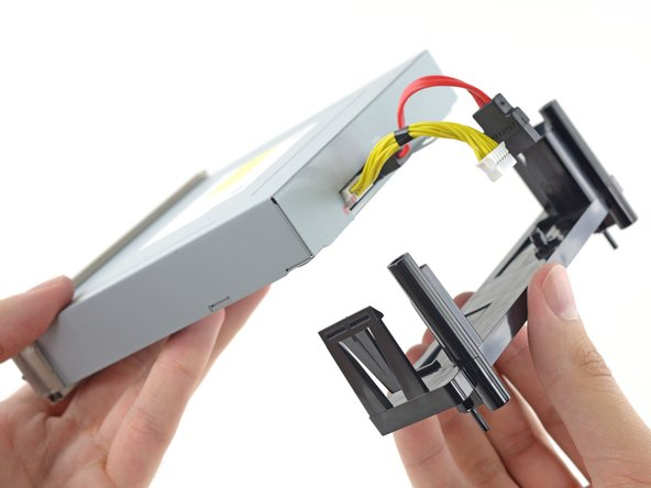 Push the clips outward and then slide the tray off the drive.