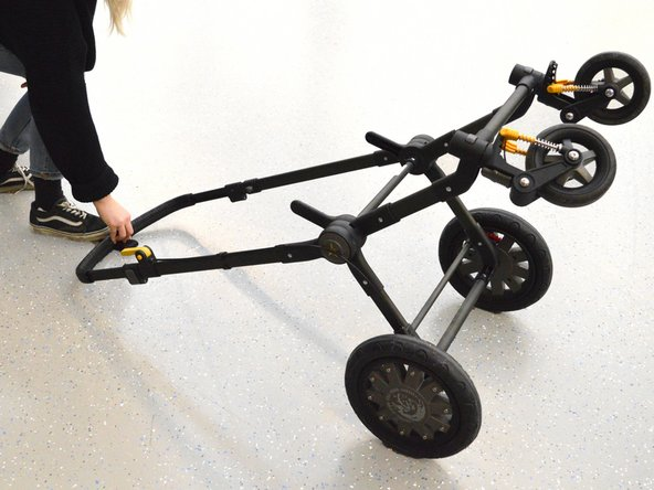 Put the frame with the handle on the ground like shown in the picture, to have better access to the swivel wheels.
