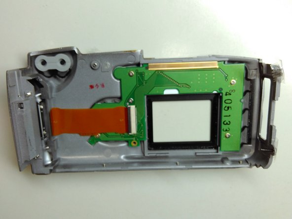 Pull the flat cable from the connector and you'll have completely removed the back casing from the camera.