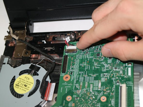 Remove the power adapter cable from the motherboard by sliding the cable out of its socket.