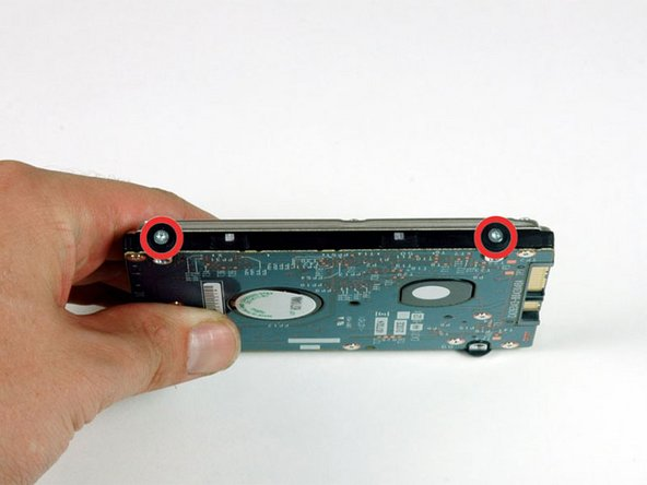 Remove the two silver T6 Torx screws and black rubber bumpers from the right side of the hard drive.