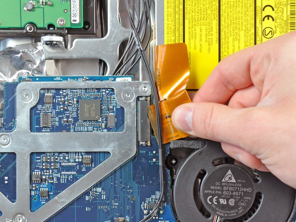 Image 3/3: Pull the optical drive ribbon cable out of its socket, being careful not to rip it in the process.