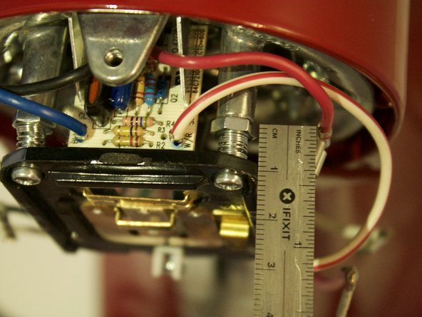 Before beginning to remove the screws, use a ruler and measure how far the screws are in. These screws determine the speed of the mixer, and not screwing them back in to the same position will change the speed of the mixer.