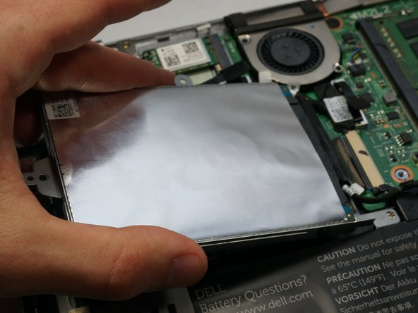 Lift the hard drive from the left side as depicted and remove.