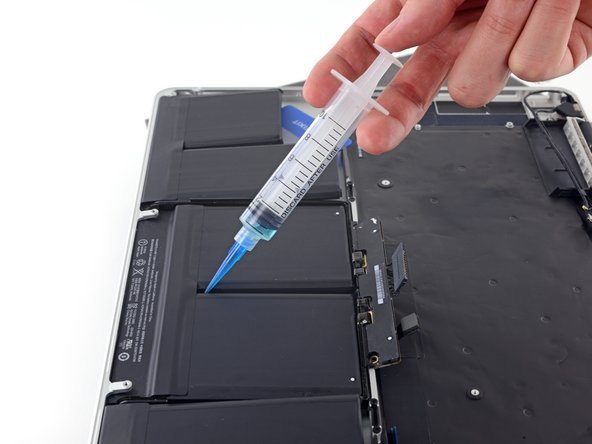 With the left edge of your MacBook Pro still propped up, apply a small amount (about 1 ml) of adhesive remover  down the center line between the two middle battery cells.