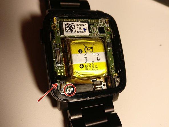 unten Links wird vorsichtig ein Flexband hochgeklappt und so gelöst.. Darunter wird eine weitere Schraube sichtbar.