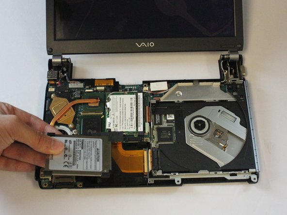 Slide the hard drive out, towards the left side of the case, while your fingers apply pressure to the ribbon cable.