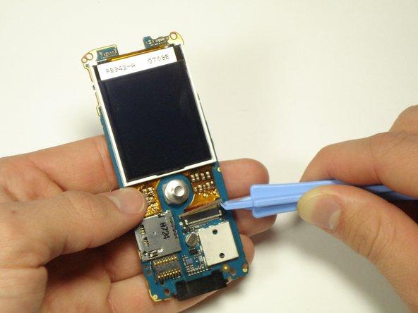 L'extrémité en cuivre du ruban devrait glisser hors du boîtier lorsque vous retirez l'écran LCD de la carte mère.