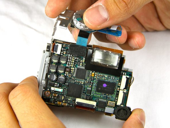 Pull off the top button piece. You will have to detach a small blue ribbon cable.