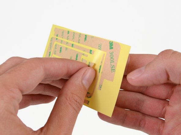 Carefully peel off the first trapezoidal adhesive strip.