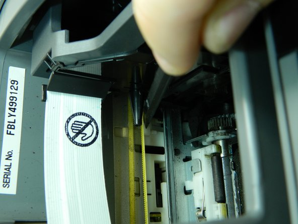 Use the flat end of the spudger to push the white button next to the ink cartridge carrier.