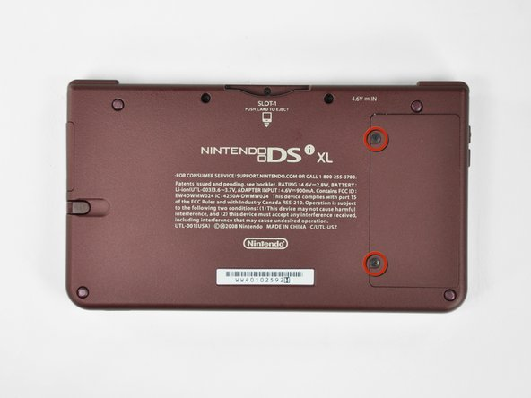 Image 1/2: Lift the battery cover off the back of the DSi XL.