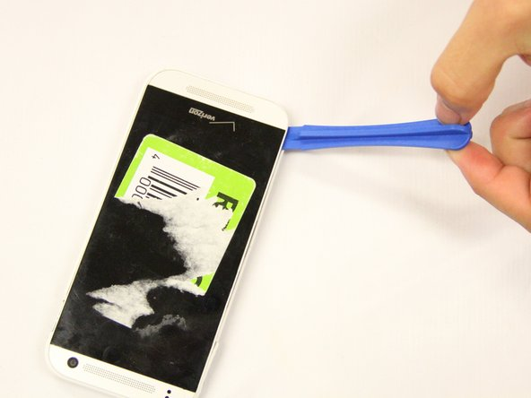 Use the plastic spudger to pry off the back cover. Place the tool in the SIM card insert and lift off the back cover with force. Continue to do this all around the phone.