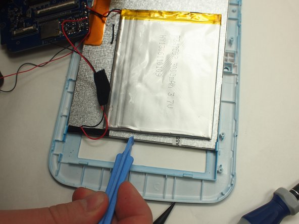 Use the plastic opening tool to slowly pry each side of the battery up.