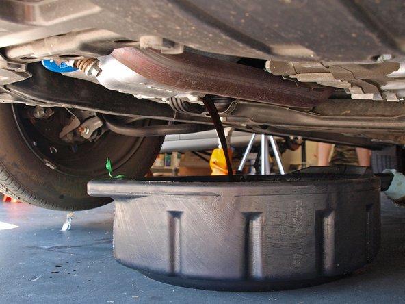 用手继续拧松直到取下, 旧机油就会流出, 落在刚才准备好的机油盆里.
