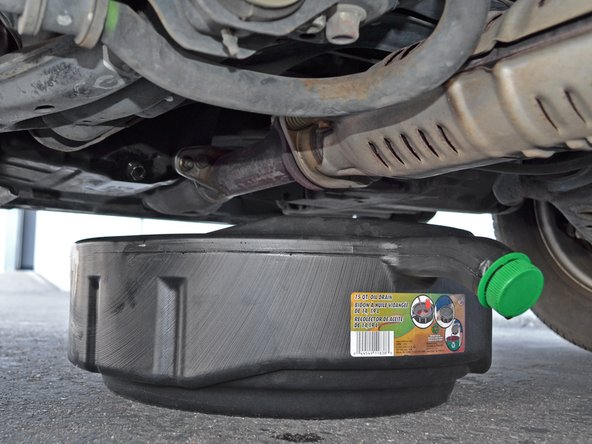 Move the oil drain pan so it will catch any oil that spills when you remove the oil filter.