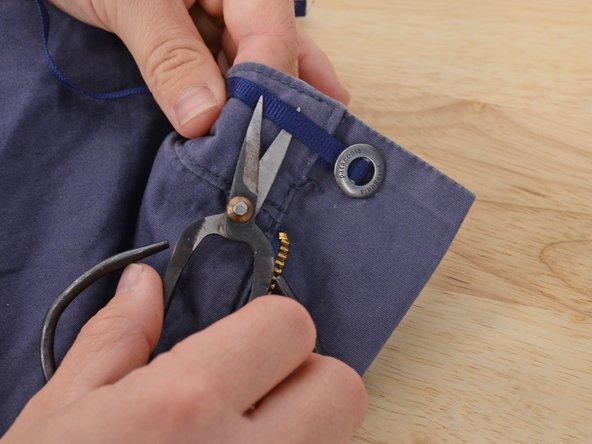 Knopf und Band umklappen, sodass die andere Seite des Knopfes nach oben zeigt. 